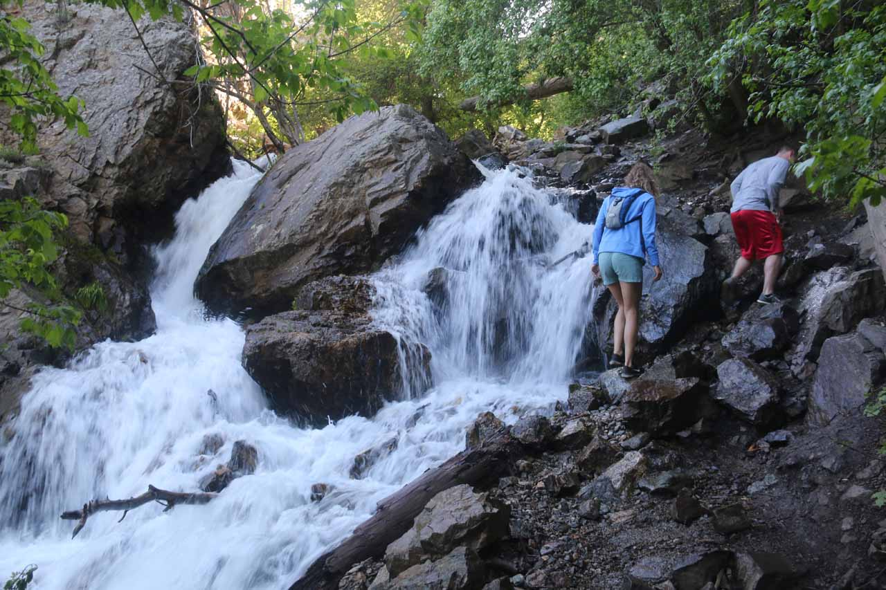 A pair of hikers scrambling above this cascade as part of the Adams Canyon Trail