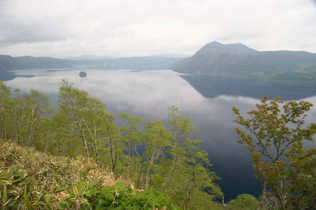 View of Lake Mashu under cloudy skies from the paid overlook
