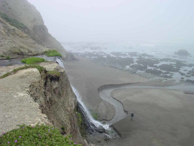 Alamere_065_05082004 - Context of Julie down by the base of Alamere Falls with the waves in low tide revealing some interesting rock formations. This was seen from the brink of the falls on a foggy morning in May 2004
