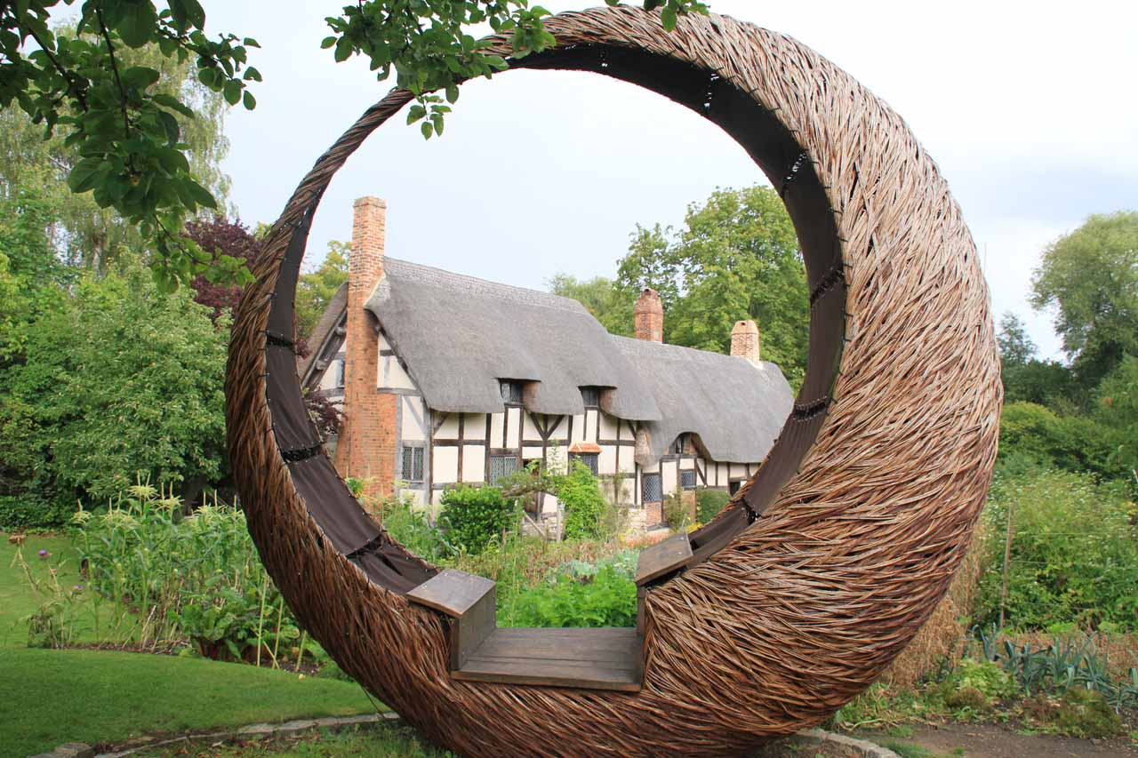 A straw structure framing the Anne Hathaway Cottage