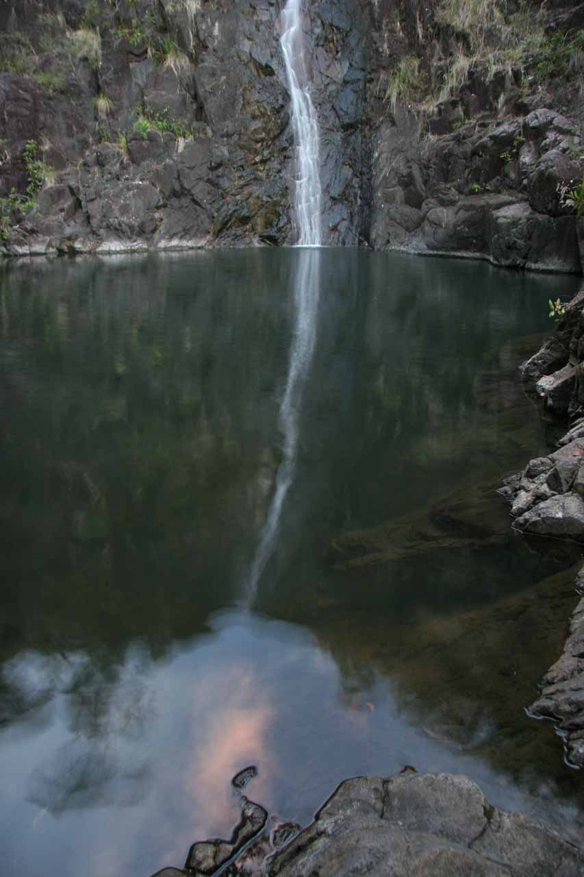 The calm reflective pool reflecting Attie Creek Falls