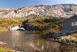 Aursjovegen_119_07162019 - A cabin and alpine tarn next to it while driving along the Aursjøvegen toll road