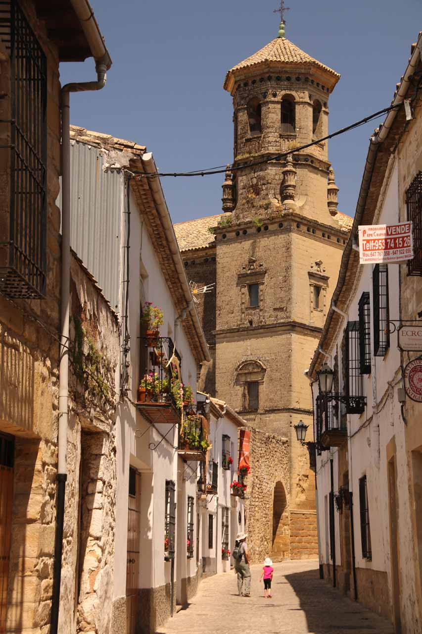 Julie and Tahia walking one of the narrow streets leading with a tower from the Antigua Universidad up ahead