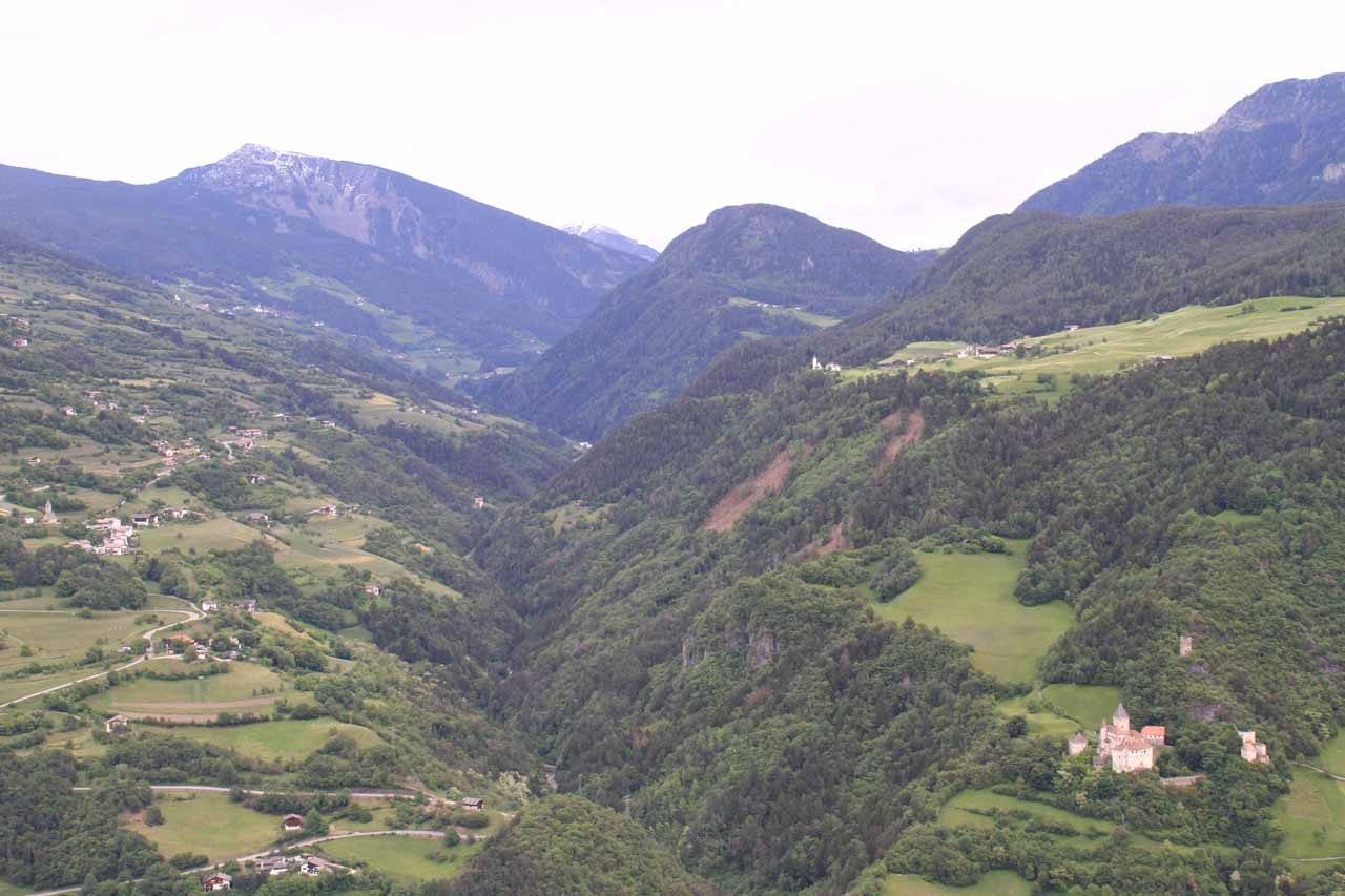 Looking back across the valley towards a castle on the lower right and some chalets and hamlets perched on mountains