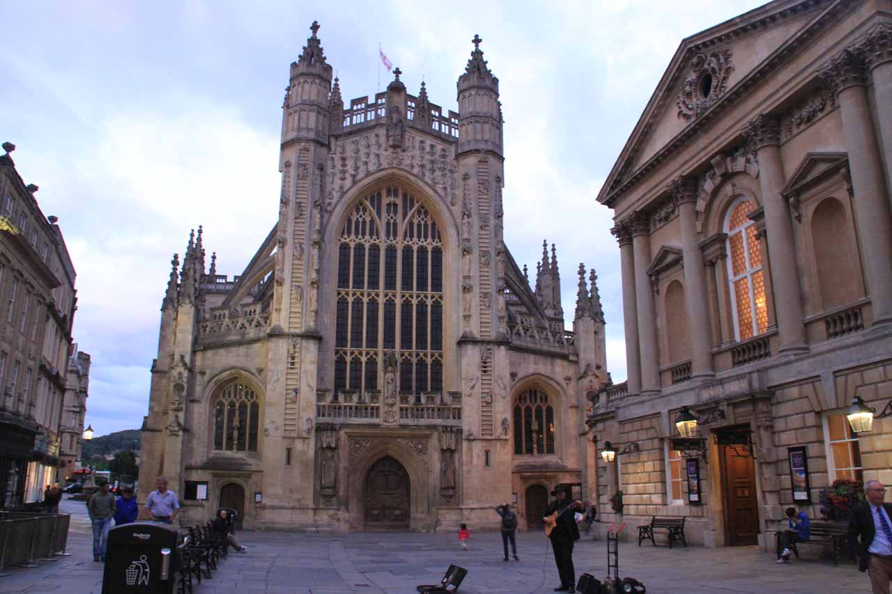 A busker entertaining a few visitors during twilight in front of both the Bath Spa entrance and Bath Abbey