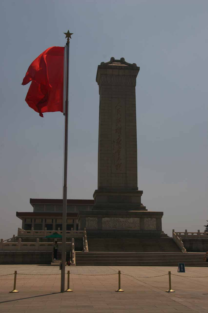 Some kind of monument before the red flag at Tiananmen Square