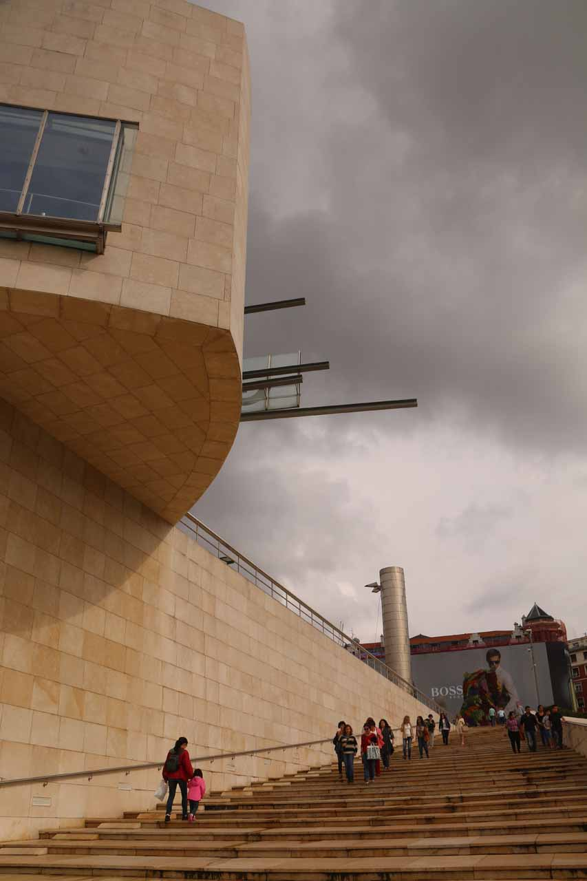 Walking up the steps to get to the entrance to the Guggenheim in Bilbao under some threatening clouds