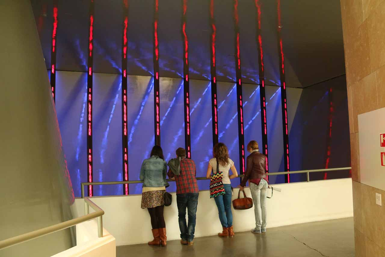 Looking at people checking out some interesting display where the contrast of colors and some words streaming on each column seemed to provoke reactions
