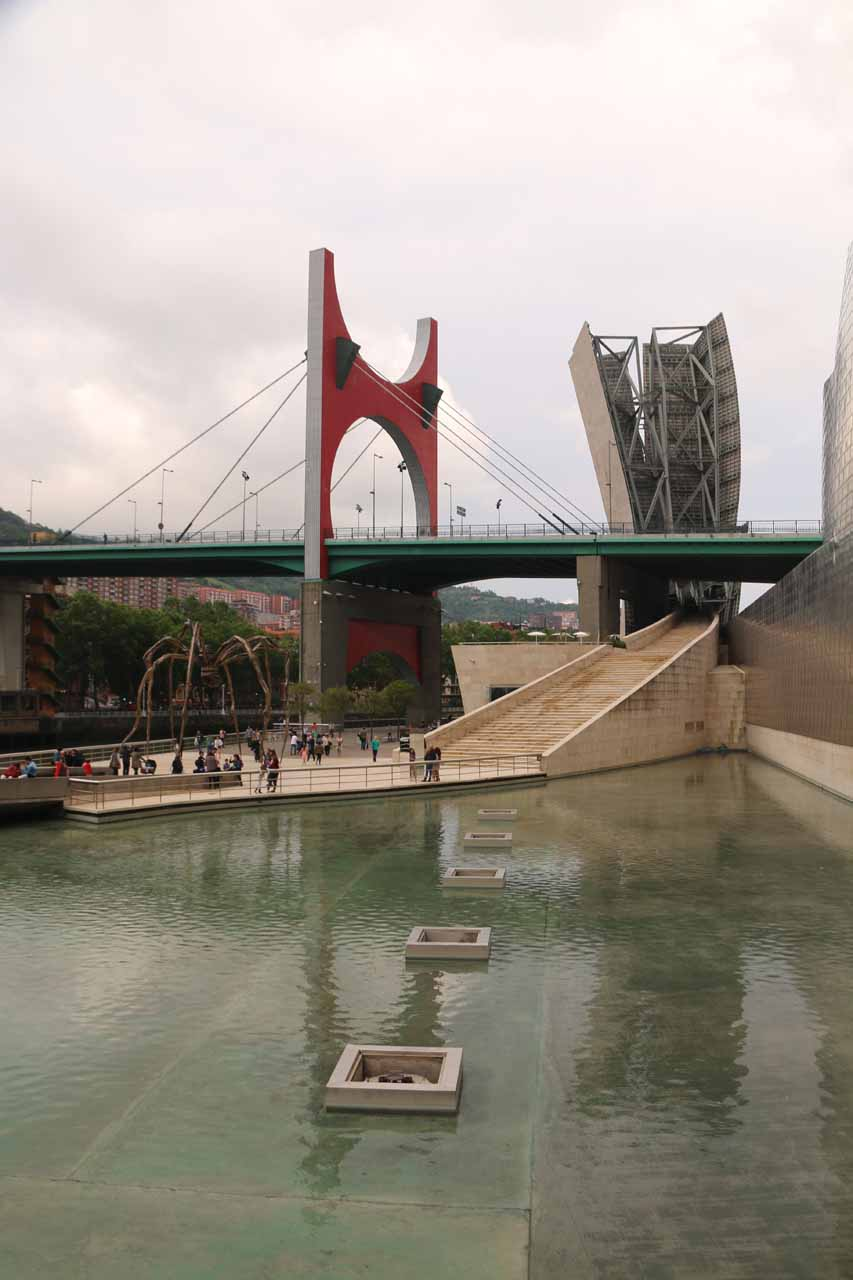 At the outside part of the Guggenheim exhibit looking towards the river and bridge over some shallow pool