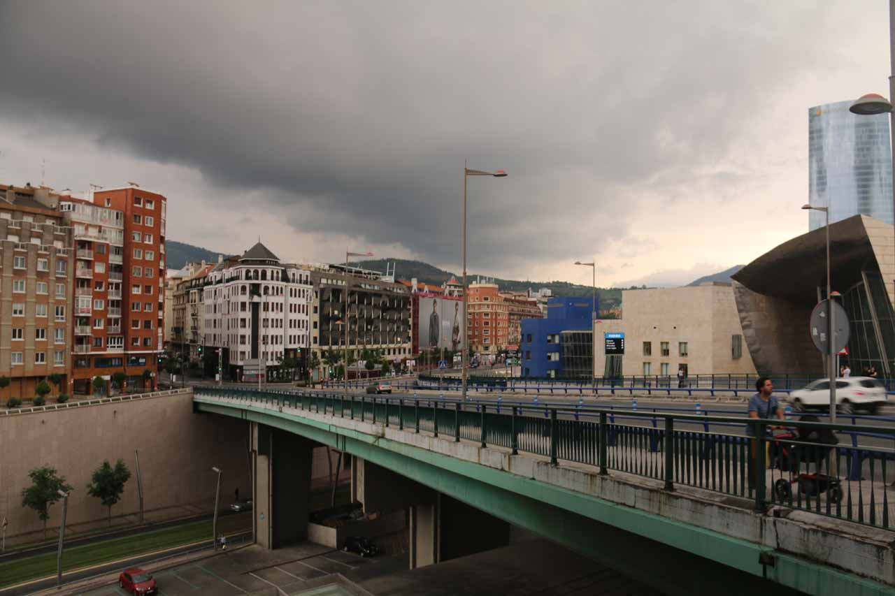 About to cross over this road bridge beneath the dark clouds near the Guggenheim Bilbao
