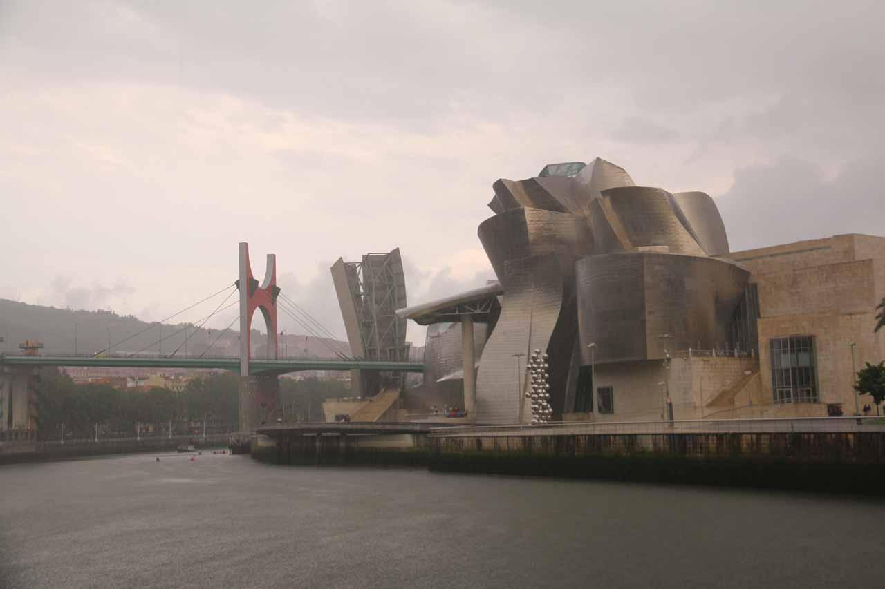 Looking back at the Guggenheim Bilbao museum under heavy rain