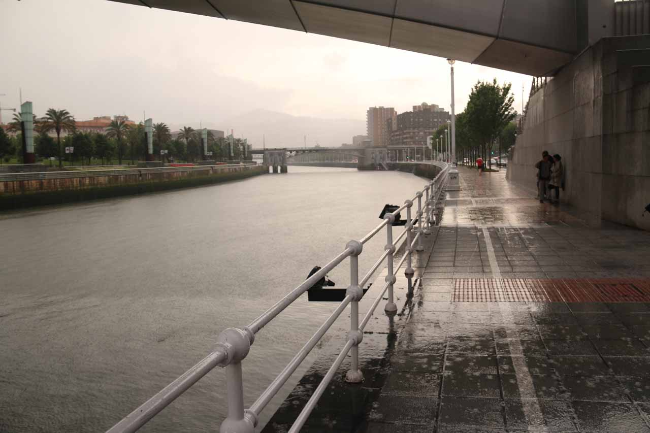 Seeking shelter beneath a pedestrian bridge (Puente Pedro Arrupe) traversing the Ria de Bilbao while the hard rain was falling