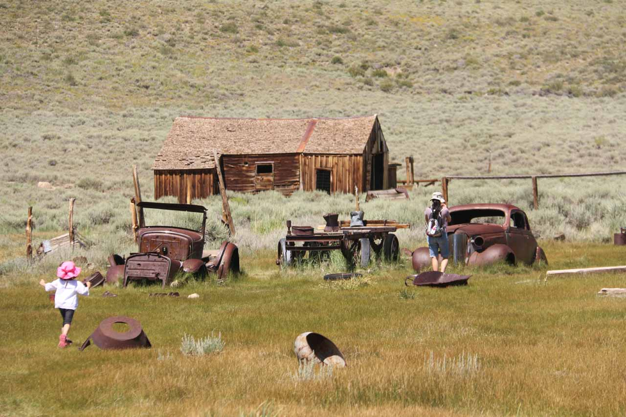 Julie and Tahia approaching some older cars in an apparent junkyard of the town of Bodie