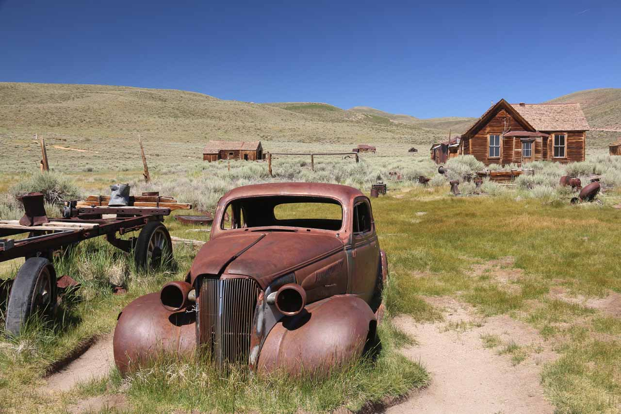 Different angled view of the old car fronting some buildings of Bodie
