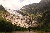 Boyabreen_043_07202019 - Another person walking towards the terminus of Boyabreen in context with the glacier and a neighboring waterfall up ahead