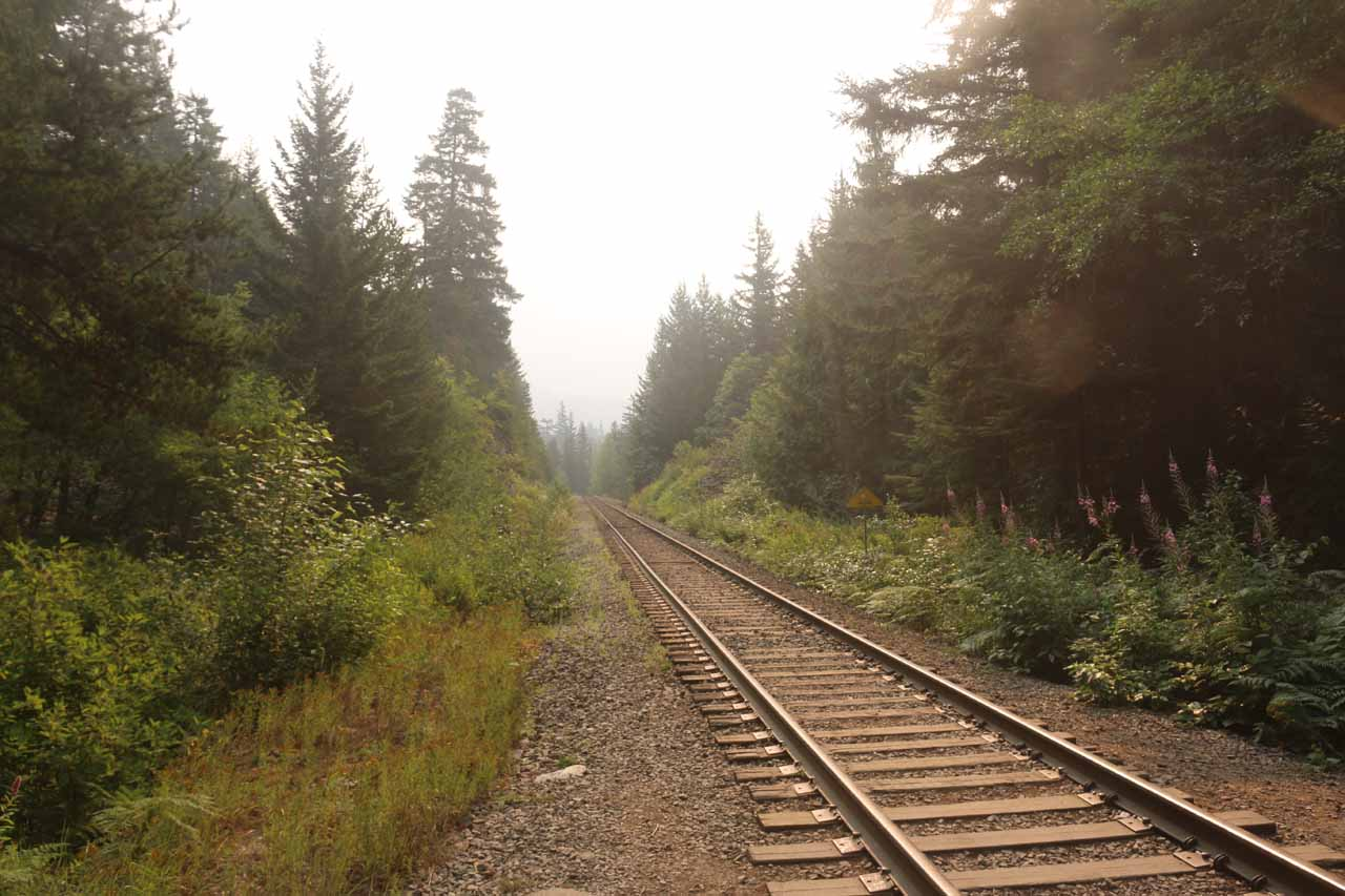 Looking along the railroad tracks with smoke hovering in the air