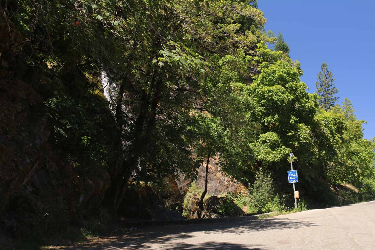 Looking back at a partial view of Bridal Veil Falls in the context of the very wide pullout adjacent to the eastbound lanes of Hwy 50