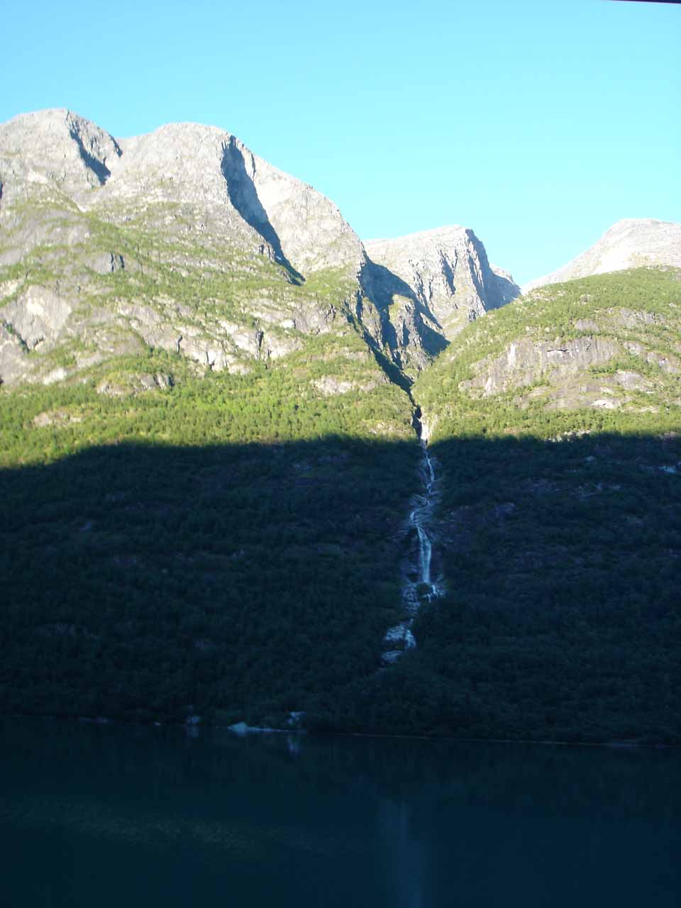 Looking back across the lake Oldevatnet towards the east-facing cliff, this thin waterfall might be on Nesleelva so it might be called Neslefossen