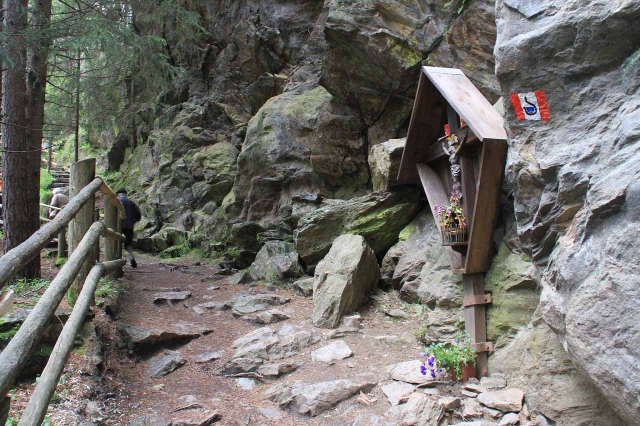 Passing by a shrine near a trail junction beyond the third waterfall