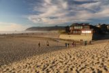 Cannon_Beach_17_052_08172017 - Late afternoon contextual look at the north end of Cannon Beach with some buildings in the foreground and many people enjoying the gorgeous weather