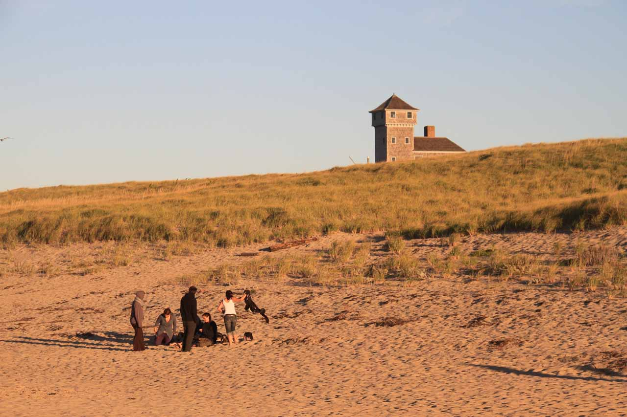 A group of youngsters and some building in the distance at Race Point Beach