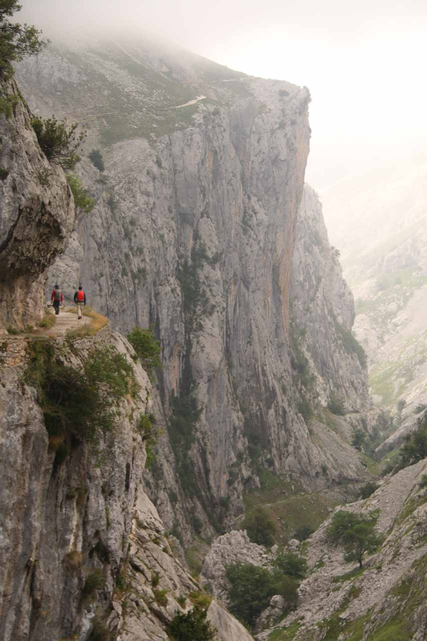 Looking back at the context of a pair of hikers on the cliff-hugging trail with the vertical cliff near Poncebos further ahead