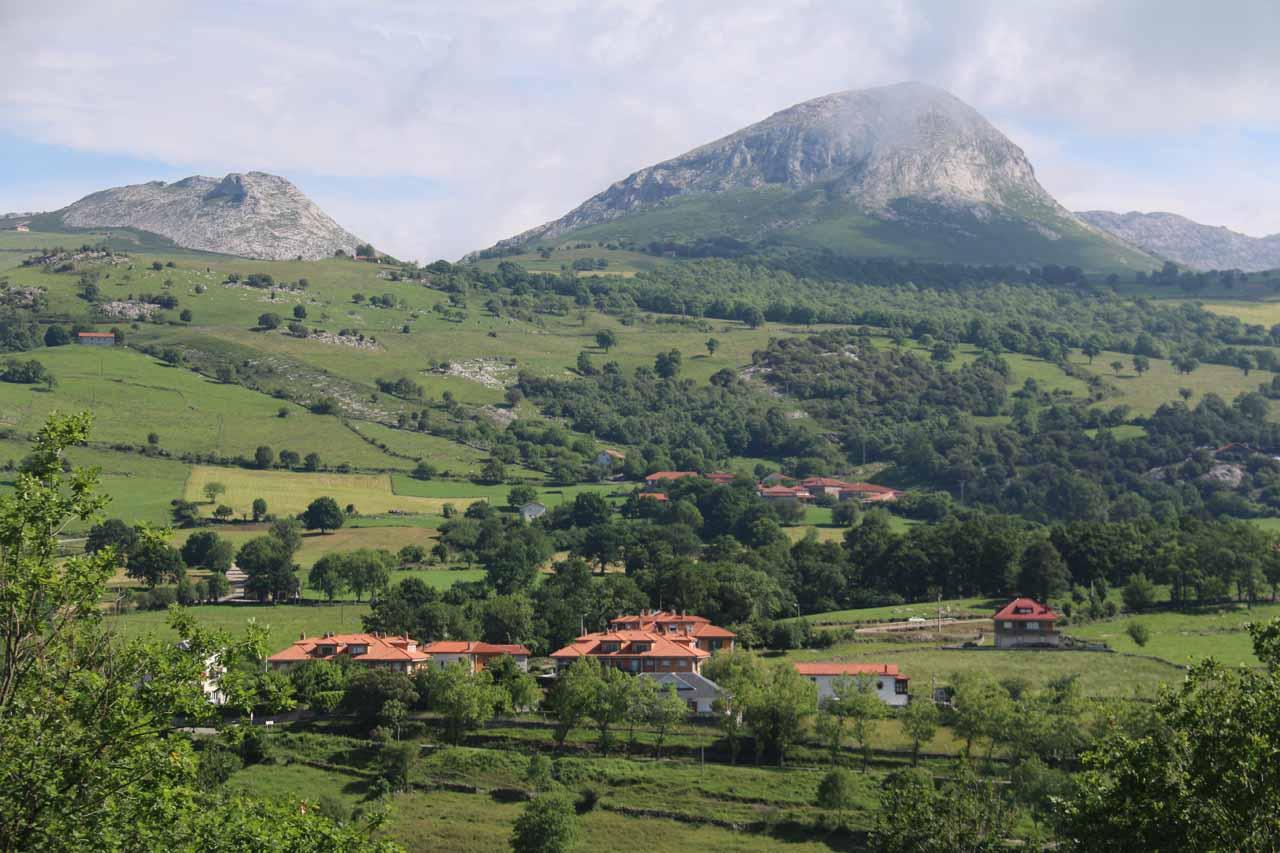 Looking over some buildings towards shapely mountains backing the scene on the way to the mirador de Cascada La Gandara