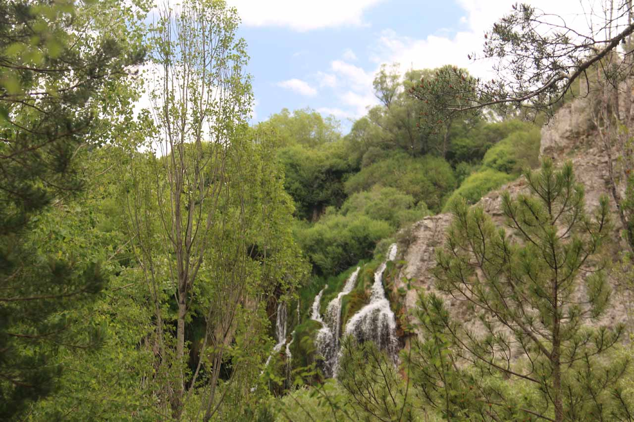 This was a partial distant view of the Cascada del Molino between trees
