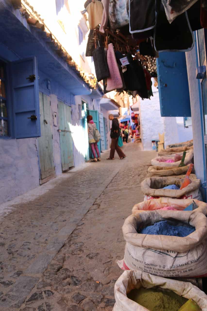 Colorful blue and green paint powders or dyes lining the alleyways of Chefchaouen