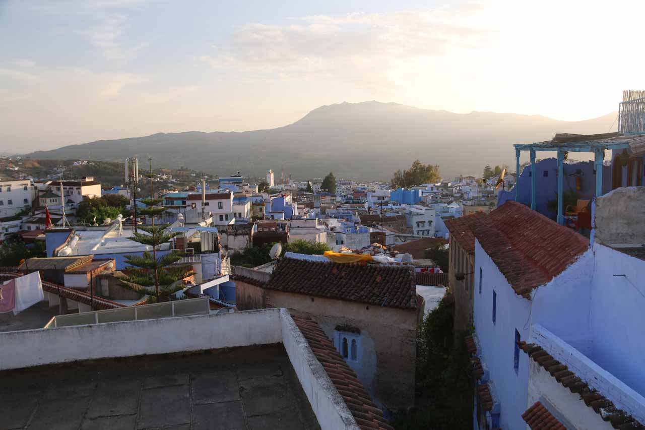 Looking out towards the medina of Chefchaouen with the setting sun hiding behind some mountains and buildings to the right