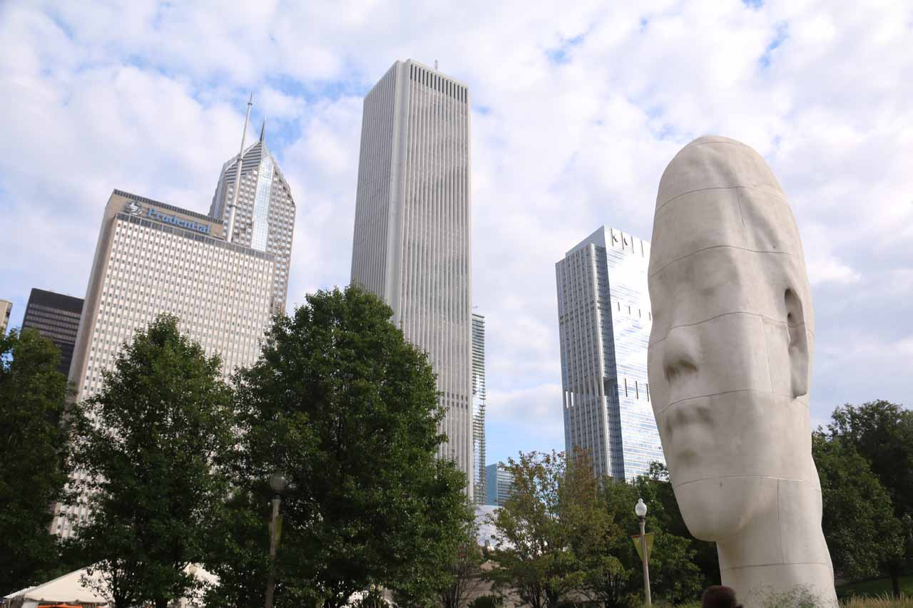 Head statue fronting some skyscrapers in the distance from Millenium Park