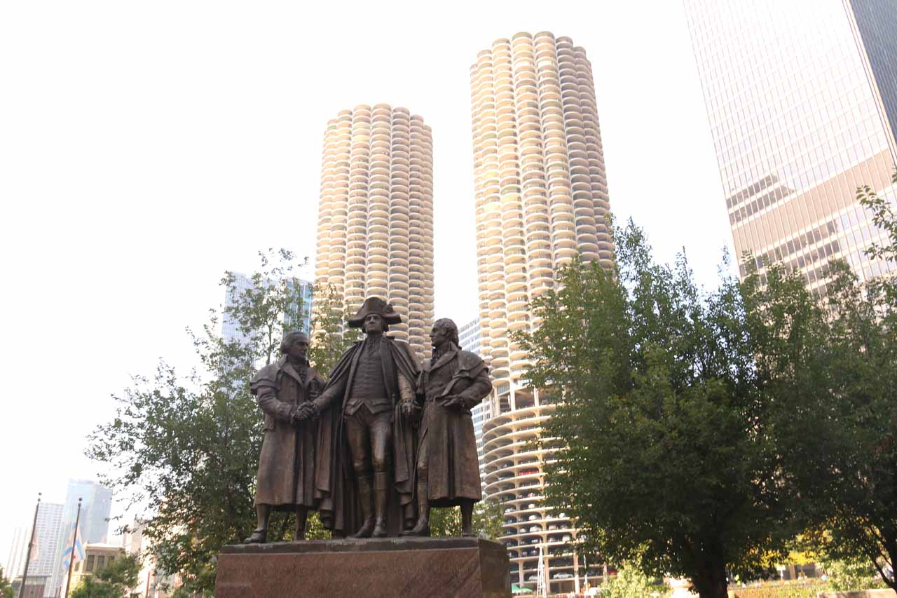 Some statues fronting cylindrical high rises with large car parks along the Chicago River Walk
