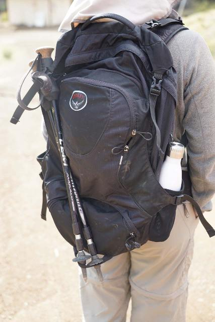 Julie using one of the side pockets of her Osprey Ozone 46 pack to hold her stainless steel water bottle