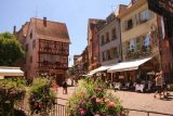 Colmar_097_06202018 - Back at the Place de la Douane looking towards some half-timbered homes fronted by flowers flanking a small canal in Colmar
