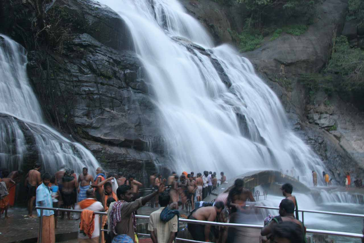 Many people taking turns getting drenched beneath the Courtallam Main Falls and its Ayurvedic properties