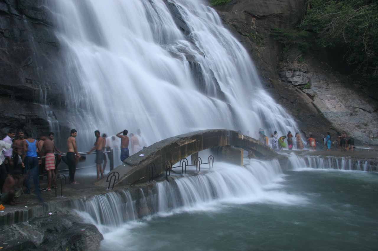 Lots of people bathing beneath the main Courtallam Falls