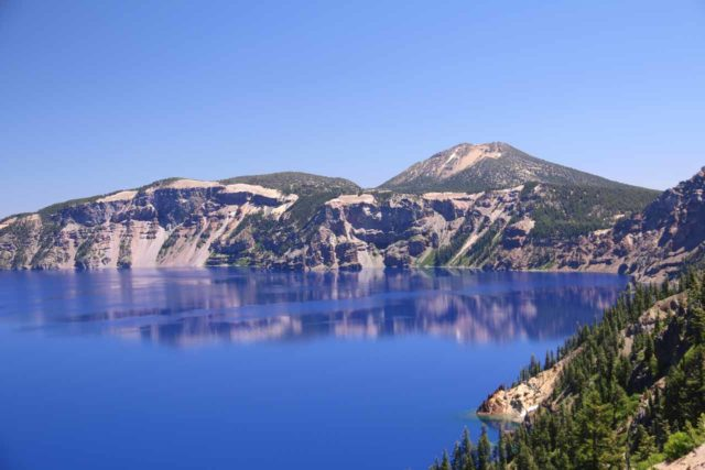 Crater_Lake_334_07152016 - Looking across the deep sapphire blue Crater Lake towards the East Rim, where the rim of the lake was reflected in its calm waters