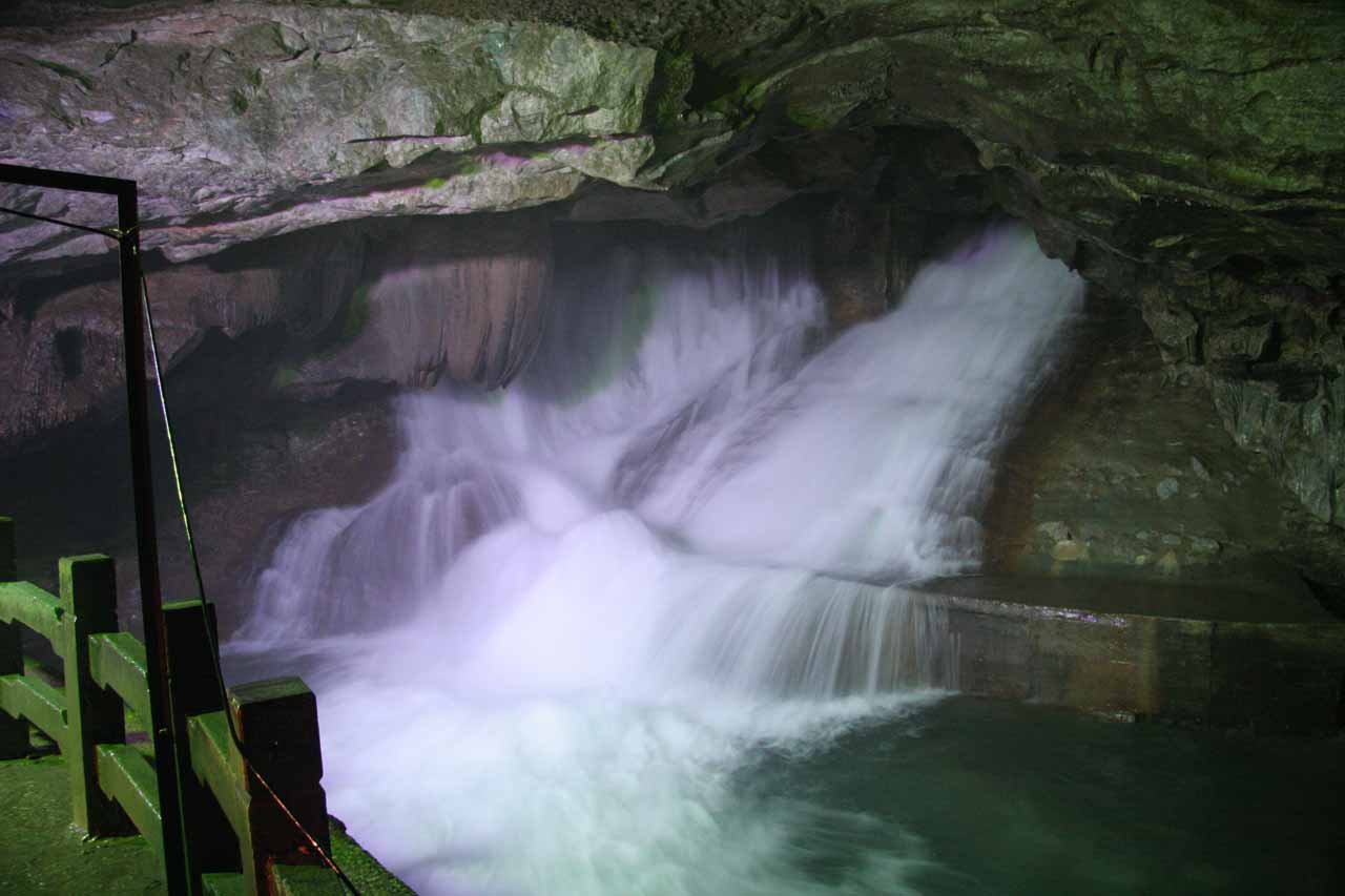 Contextual look at the Crown Cave Waterfall showing the misty lookout platform
