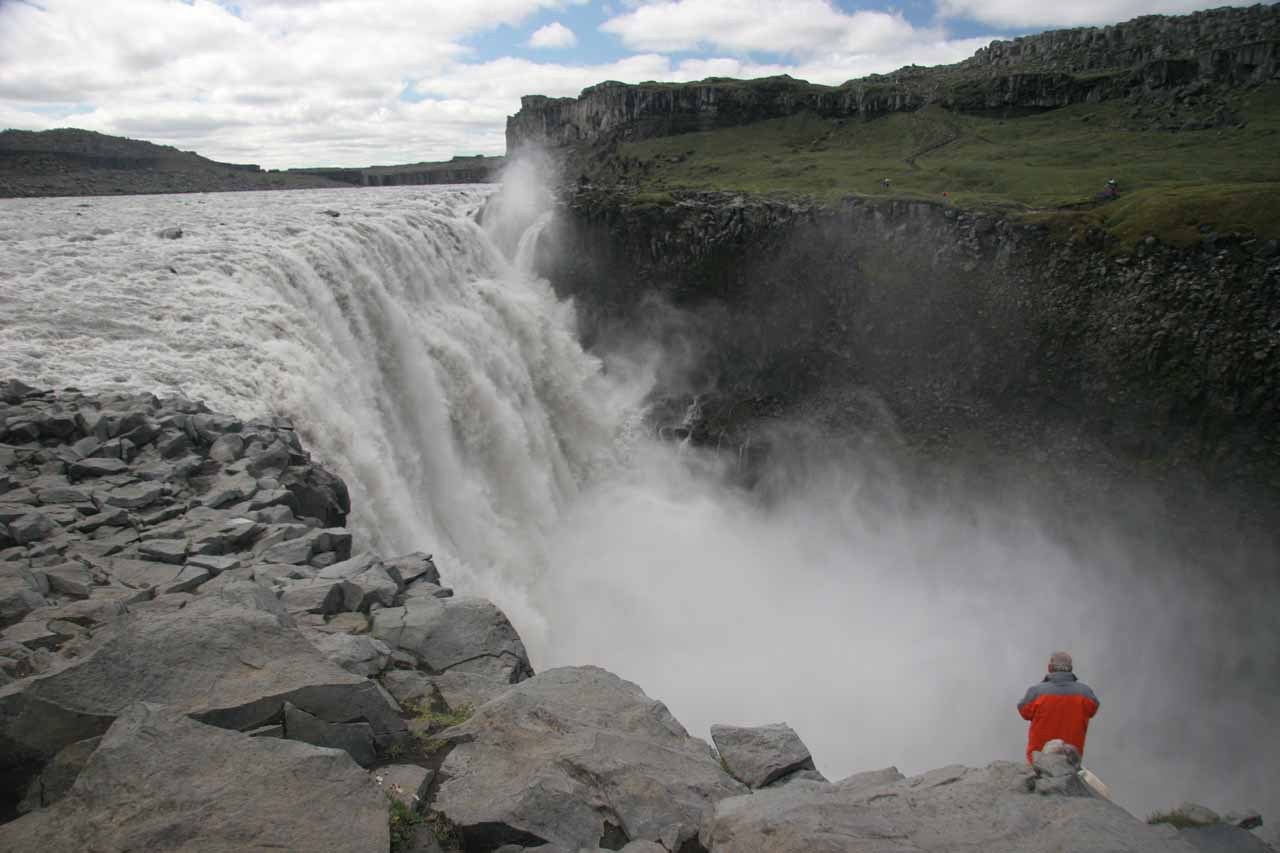 Looking at some guy get quite close to the brink of the cliff by Dettifoss
