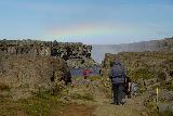 Dettifoss_136_08122021 - Looking back at some hikers making their way from the east side of Dettifoss to Selfoss with more bold rainbows arcing across the mist of Dettifoss