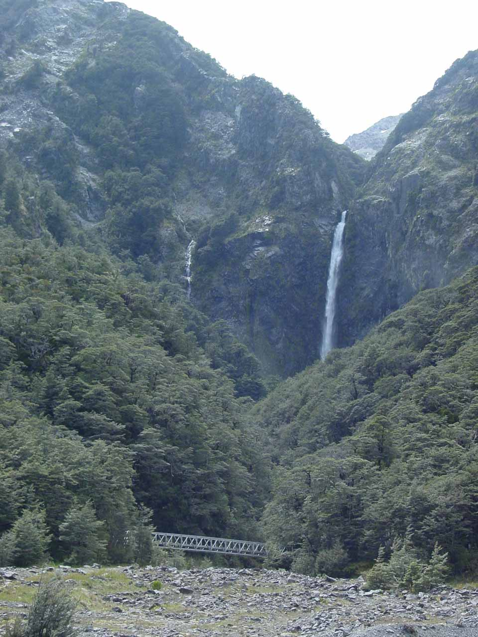Approaching the bridge traversing the Bealey River with Devils Punchbowl Falls looming large over the scene