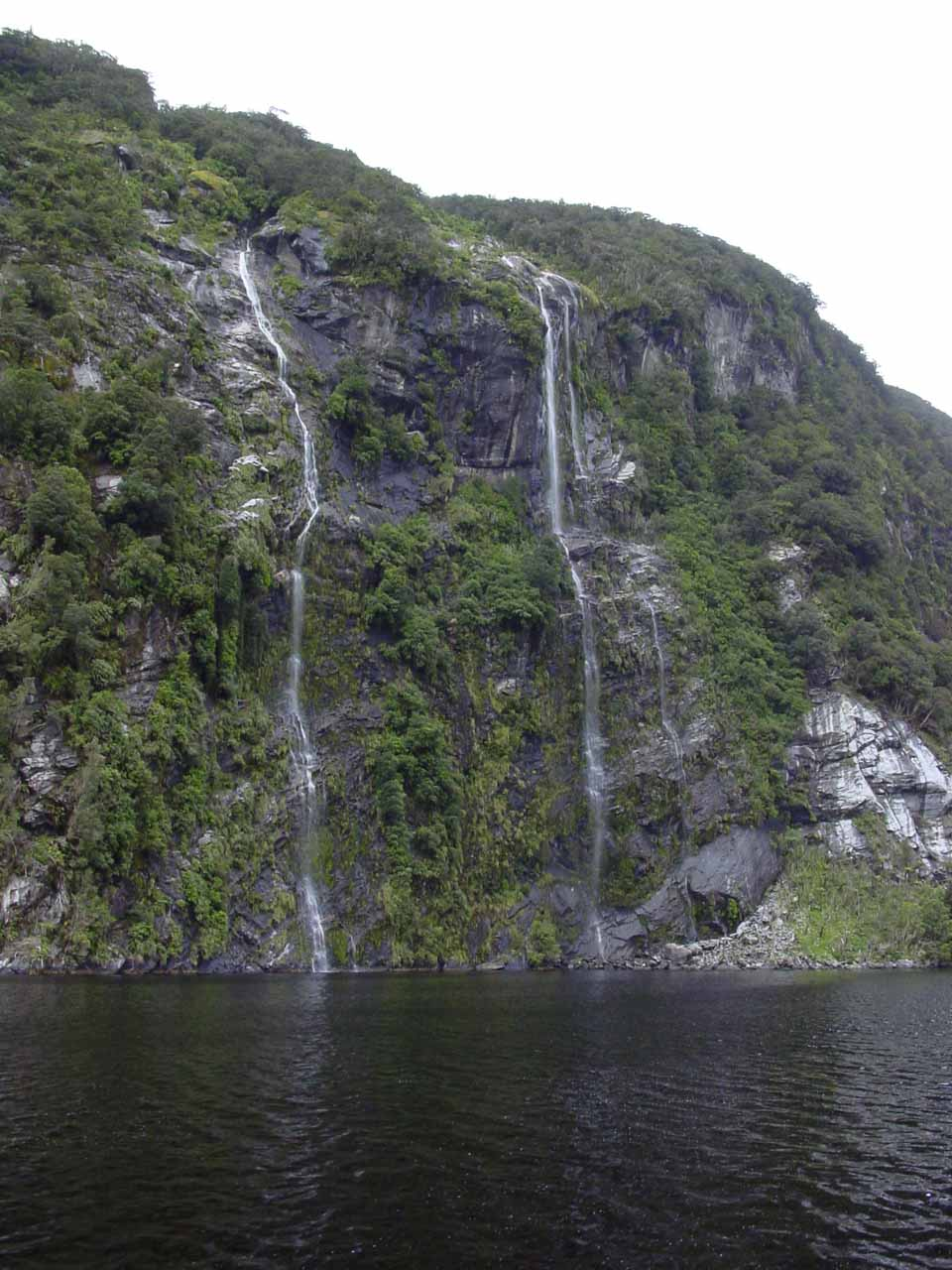 A pair of thin ephemeral waterfalls spilling into Doubtful Sound near Commander Peak