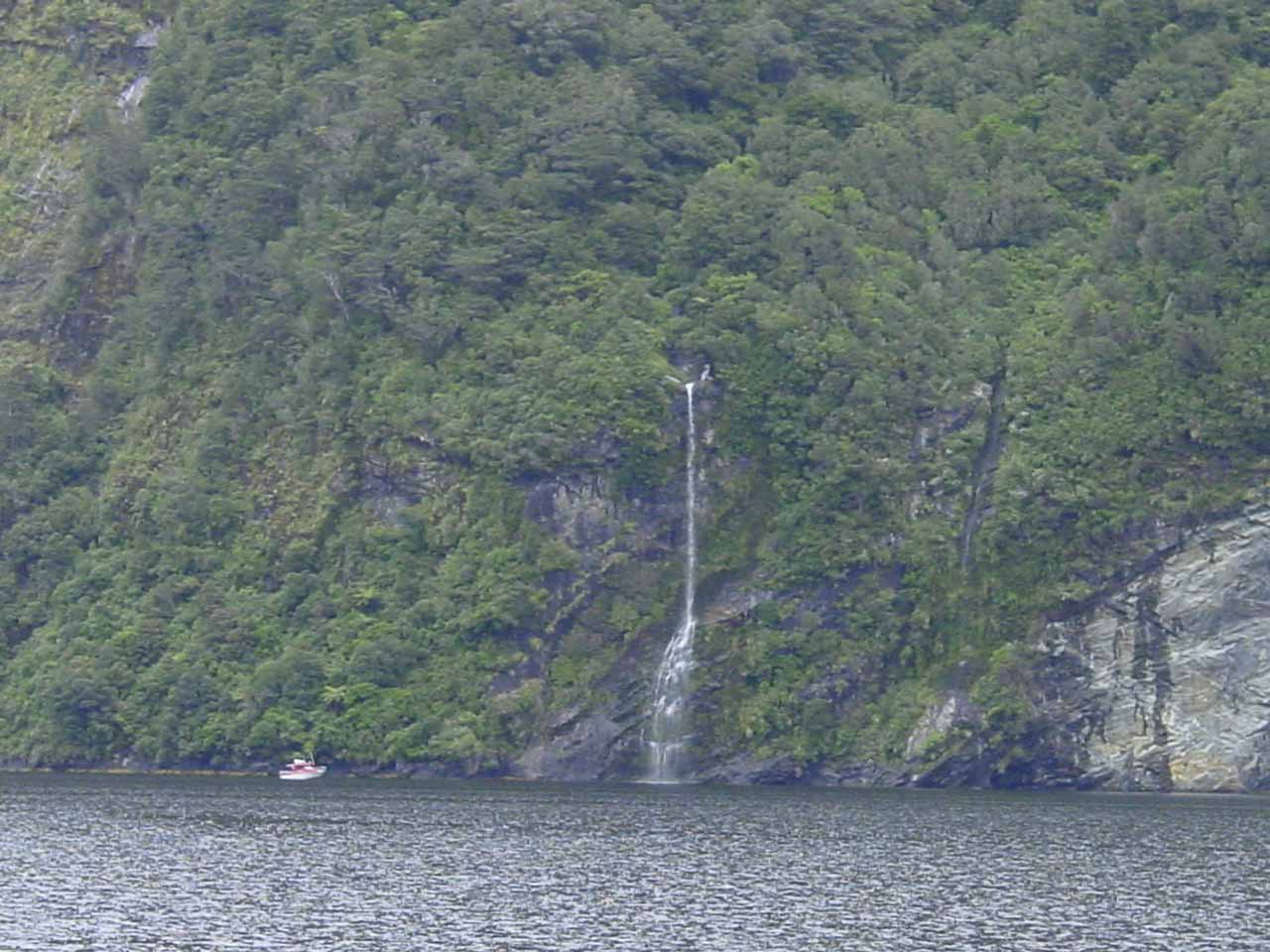 A small craft dwarfed by a thin waterfall in one of the side arms of Doubtful Sound