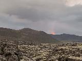 Drive_from_Volcano_to_Reykjavik_018_iPhone_08192021 - Another look towards the fire on the mountain of the Fagradalsfjall Volcano as seen across a lava field north of Grindavik