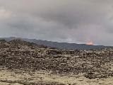 Drive_from_Volcano_to_Reykjavik_021_iPhone_08192021 - Another look towards the fire on the mountain of the Fagradalsfjall Volcano as seen across a lava field north of Grindavik