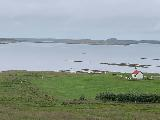Drive_to_Snaefellsness_053_iPhone_08172021 - Looking in the distance towards a church or farm bordering the body of water to the north along the northern side of the Snaefellsnes Peninsula