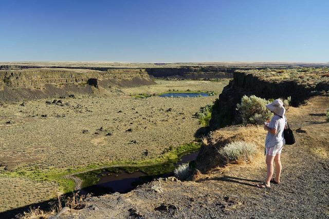 Dry_Falls_057_06192021 - Julie checking out the more downstream parts of Dry Falls, but we're still unable to see (without a drone or from the elevated confines of the visitor center) the other two-thirds of the waterfall due to the long butte in the way on the topleft of this picture