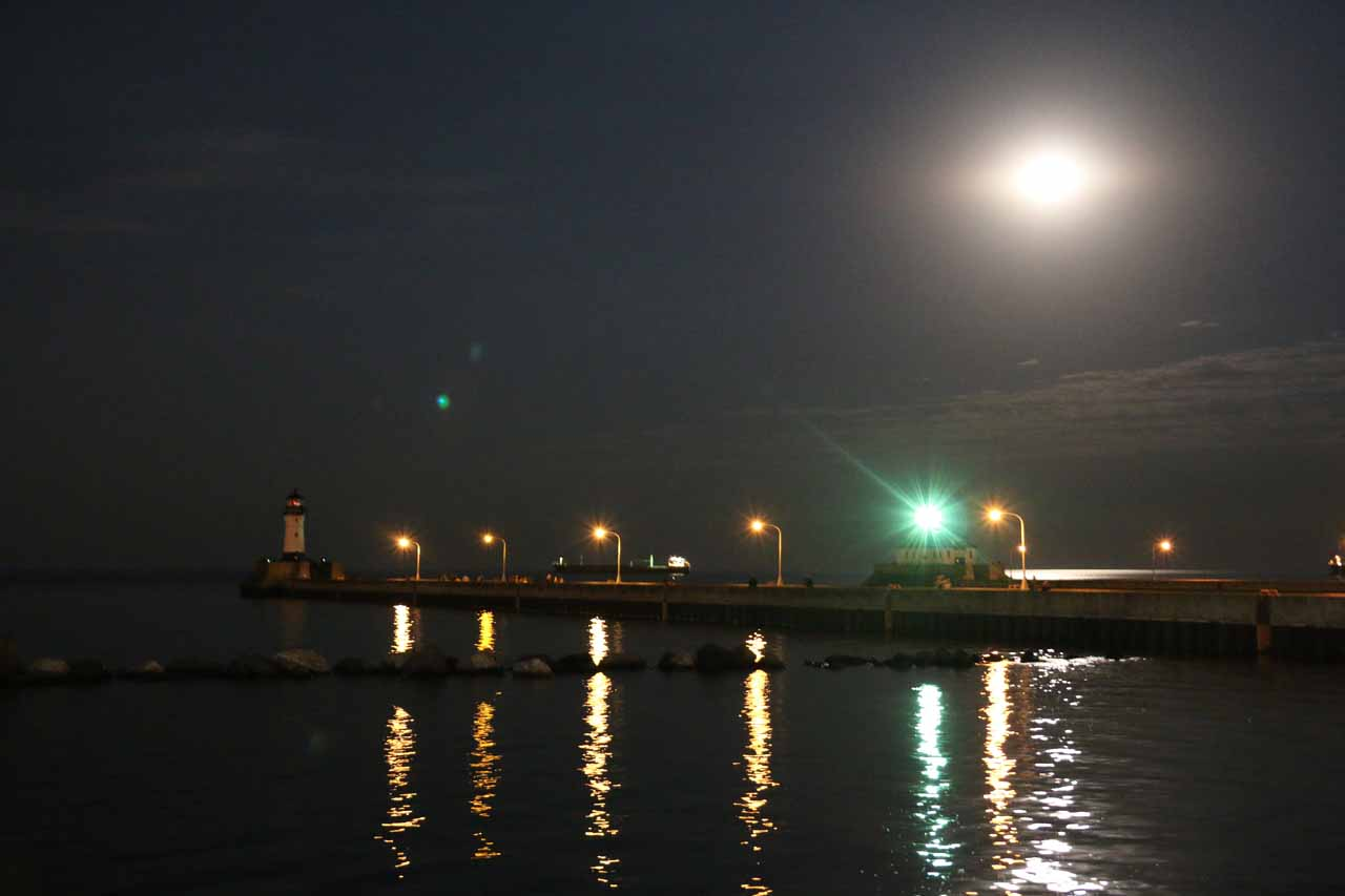 The bright moon over the pier and lighthouse on the Lake Superior waterfront in Duluth