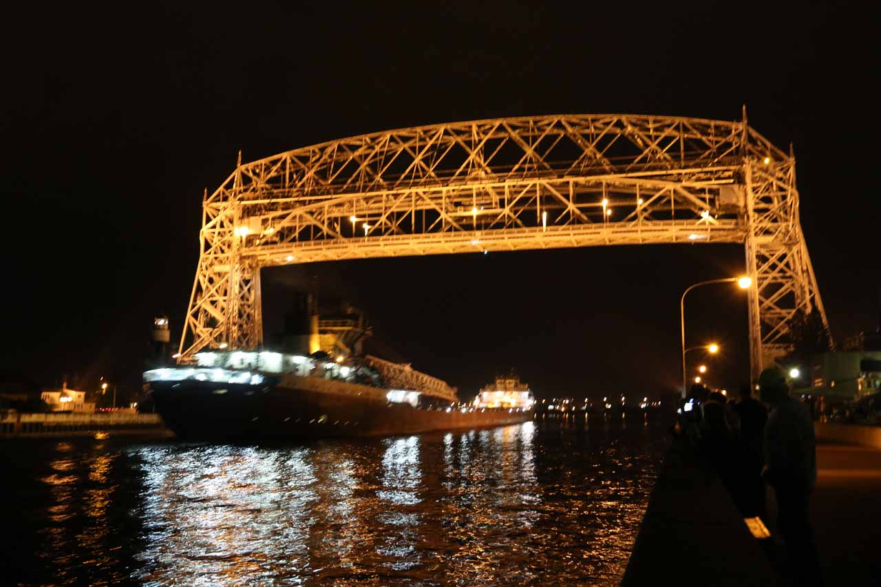 A giant barge passing beneath the iconic bridge in Duluth