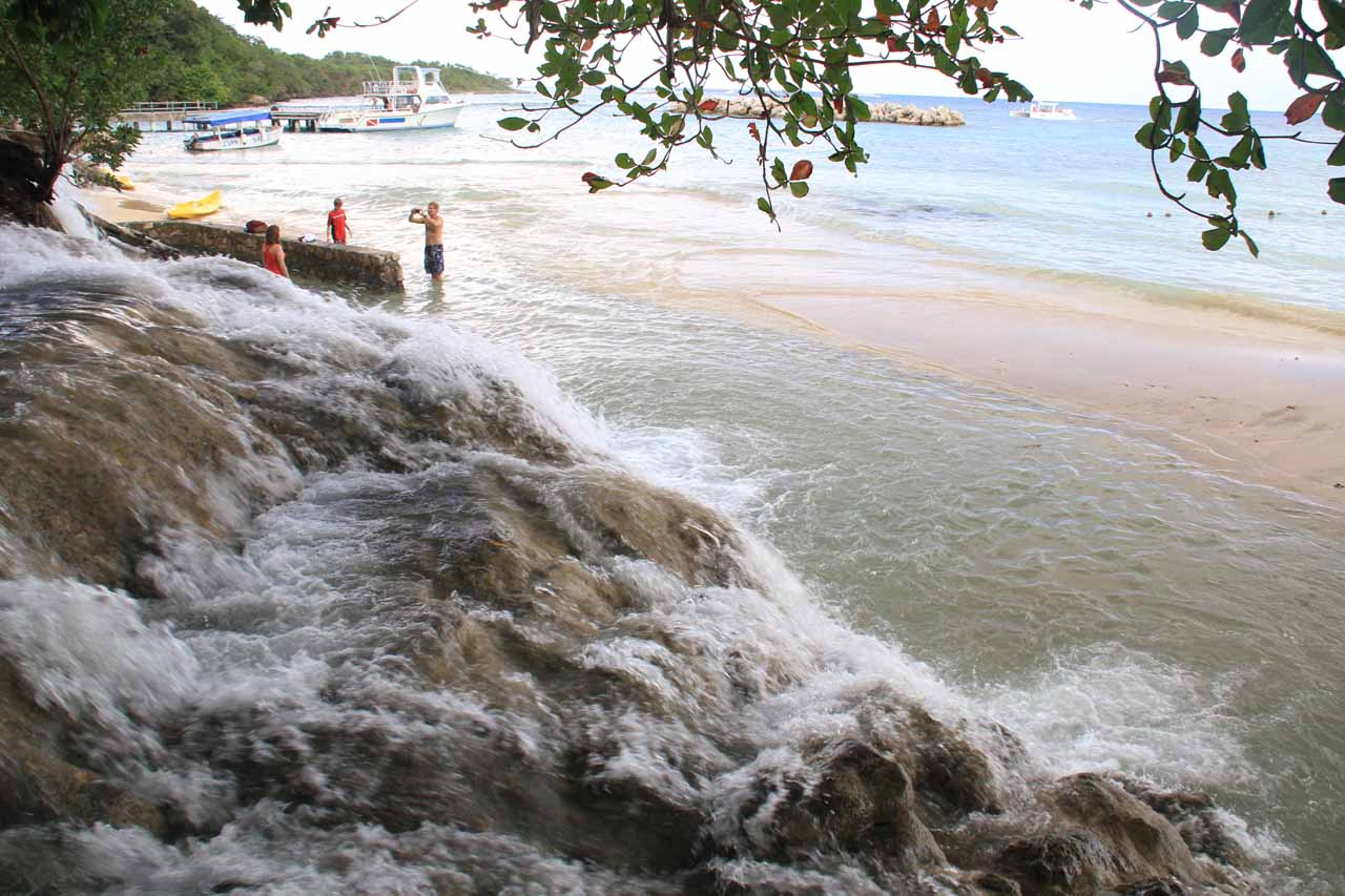 Looking over the bottommost cascade of Dunn's River Falls towards the colorful Caribbean Sea